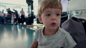 Smutny dziecka obsiadanie na torbach w poczekalni zbiory wideo