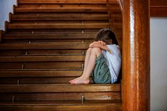 Smutny dziecko, siedzi na schody w dużym domu, pojęcie dla bu zdjęcie stock