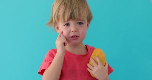 Smutny dziecko z mango w ręce zbiory wideo