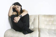 Smutny dziewczyny obsiadanie na kanapie Obrazy Stock