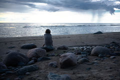 Smutny dziewczyny obsiadanie na skałach plaża zawijająca w ręczniku Zdjęcie Stock