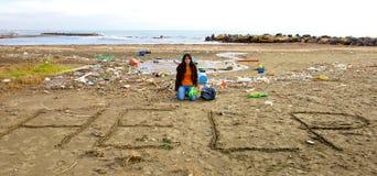 Smutny ekolog pyta dla pomocy obsiadania na plażowy pełnym brud zdjęcie royalty free