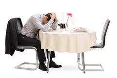 Smutny facet siedzi samotnie przy restauracyjnym stołem obraz stock