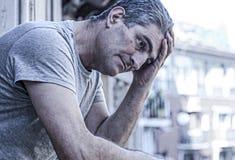 Smutny i przygnębiony 40s mężczyzna patrzeje przez outdoors balco w domu fotografia royalty free