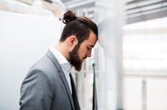 Smutny i sfrustowany młody biznesmen w kostium pozycji w biurze, głowa przeciw ścianie obraz royalty free