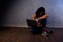 Smutny i straszący żeński nastolatek z komputerowy laptopu cierpienia cyberbullying i napastowanie jest onlinym uczuciem zdjęcia stock