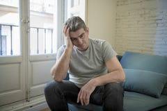 Smutny i zmartwiony mężczyzna z popielaty włosiany obsiadanie leżanki patrzeć w domu zdjęcie royalty free