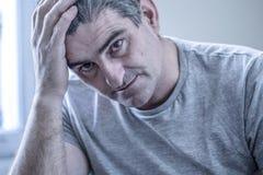 Smutny i zmartwiony mężczyzna z popielaty włosiany obsiadanie leżanki patrzeć w domu zdjęcia royalty free