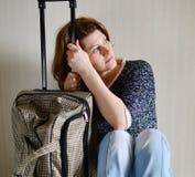 Smutny kobiety obsiadanie blisko ściany z walizką ponieważ rozwód obrazy stock