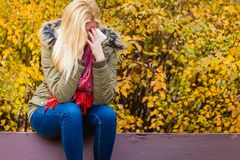 Smutny kobiety obsiadanie na ławce w parkowej chuje twarzy Obrazy Royalty Free
