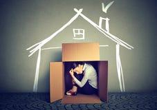 Smutny kobiety obsiadanie w pudełko domu w rewizi dla schronienia Fotografia Royalty Free