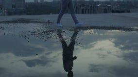 Smutny mężczyzna chodzi samotnie patrzejący odbicia ponury niebo w kałużach, kryzys zbiory