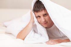 Smutny mężczyzna chuje w łóżku pod prześcieradłami Zdjęcie Royalty Free