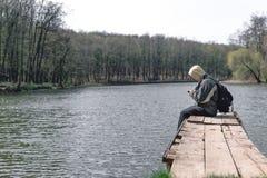 Smutny m??czyzna siedzi samotnie na molu jeziorem Las w tle kapiszon na jego g?owie plecak w r?ka chwyta telefonie zdjęcia royalty free