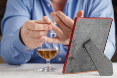 Smutny mężczyzna trzyma obrączkę ślubną blisko szkła alkoholiczka był fotografia stock