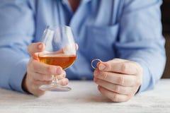 Smutny mężczyzna trzyma obrączkę ślubną blisko szkła alkoholiczka był obraz royalty free