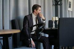 Smutny mężczyzna w garnituru obsiadaniu z telefonem w kawiarni on ` s spęczenie zdjęcia royalty free