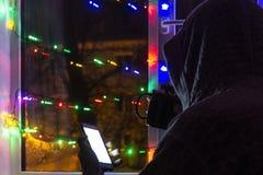smutny mężczyzna w kapiszonie z smartphone w zamazanym bokeh na tle okno dekorujący z girlandami z pustym, zdjęcia stock