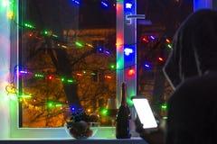 smutny mężczyzna w kapiszonie z smartphone w zamazanym bokeh na tle okno dekorujący z girlandami z pustym, obrazy stock