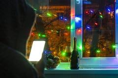 smutny mężczyzna w kapiszonie z smartphone w zamazanym bokeh na tle okno dekorujący z girlandami z pustym, zdjęcie royalty free
