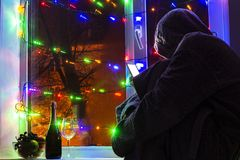 smutny mężczyzna w kapiszonie z smartphone w zamazanym bokeh na tle okno dekorujący z girlandami z pustym, zdjęcia royalty free