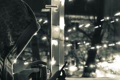 smutny mężczyzna w kapiszonie z smartphone w zamazanym bokeh na tle okno dekorujący z girlandami z pustym, obraz stock
