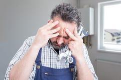 Smutny męski instalator ma migrenę obraz stock