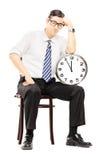Smutny męski obsiadanie na drewnianym mieniu i krześle zegar Obrazy Stock