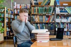 Smutny męski uczeń w bibliotece uniwersyteckiej Zdjęcie Royalty Free