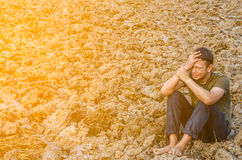 Smutny młodego człowieka obsiadanie w jałowej ziemi Z słońca światłem Fotografia Stock