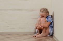 Smutny młodej dziewczyny obsiadanie w kącie Zdjęcia Royalty Free