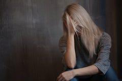 Smutny młodej kobiety obsiadanie przy ścianą Młoda blondynka Depresja i problemy fotografia stock