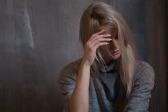 Smutny młodej kobiety obsiadanie przy ścianą Młoda blondynka Depresja i problemy zdjęcia stock