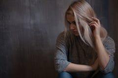 Smutny młodej kobiety obsiadanie przy ścianą Młoda blondynka Depresja i problemy fotografia royalty free