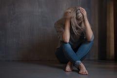 Smutny młodej kobiety obsiadanie przy ścianą Młoda blondynka Depresja i problemy obrazy stock
