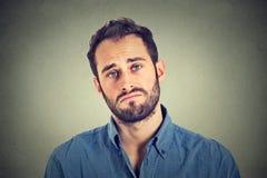 Smutny młody człowiek na szarości ściany tle obrazy royalty free