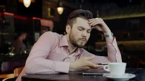 Smutny młody człowiek z telefonem komórkowym w barze zbiory