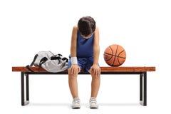 Smutny mały gracza koszykówki obsiadanie na ławce zdjęcia stock