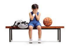 Smutny mały gracza koszykówki obsiadanie na ławce obrazy royalty free