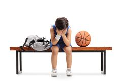 Smutny mały gracza koszykówki obsiadanie na płaczu i ławce obrazy stock