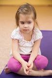 Smutny małej dziewczynki obsiadanie na macie Zdjęcie Royalty Free