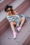 Smutny modniś dziewczyny obsiadanie na główkowaniu i schodkach zdjęcie royalty free