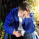 Smutny nastolatek z telefonem komórkowym Obraz Royalty Free