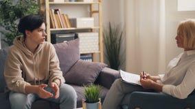 Smutny nastoletni chłopak opowiada żeński psychoterapeuty obsiadanie na kanapie w biurze