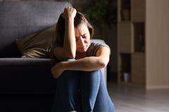 Smutny nastoletni w ciemnym żywym pokoju w domu fotografia stock