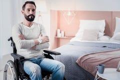 Smutny niepełnosprawny mężczyzna obsiadanie z jego rękami krzyżować obrazy royalty free