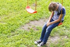 Smutny osamotniony chłopiec obsiadanie na huśtawkach Fotografia Royalty Free
