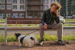 Smutny osamotniony faceta obsiadanie na ?awce z jego psem szykany adolescencja w komunikacyjnym poj?ciu zdjęcie royalty free