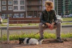 Smutny osamotniony faceta obsiadanie na ?awce z jego psem szykany adolescencja w komunikacyjnym poj?ciu obraz royalty free