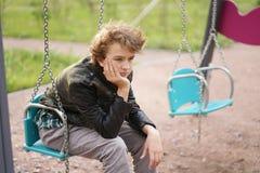 Smutny osamotniony nastolatek plenerowy na boisku szykany adolescencja w komunikacyjnym poj?ciu zdjęcie stock